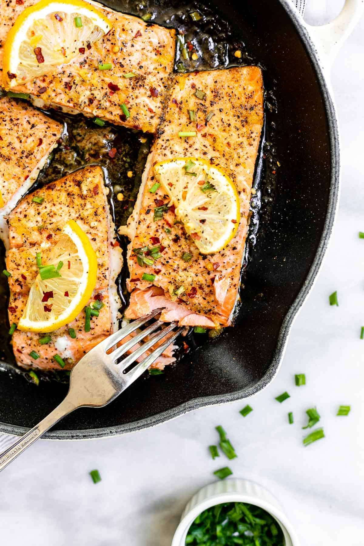 Final lemon salmon recipe in a cast iron skillet with a fork on the side.