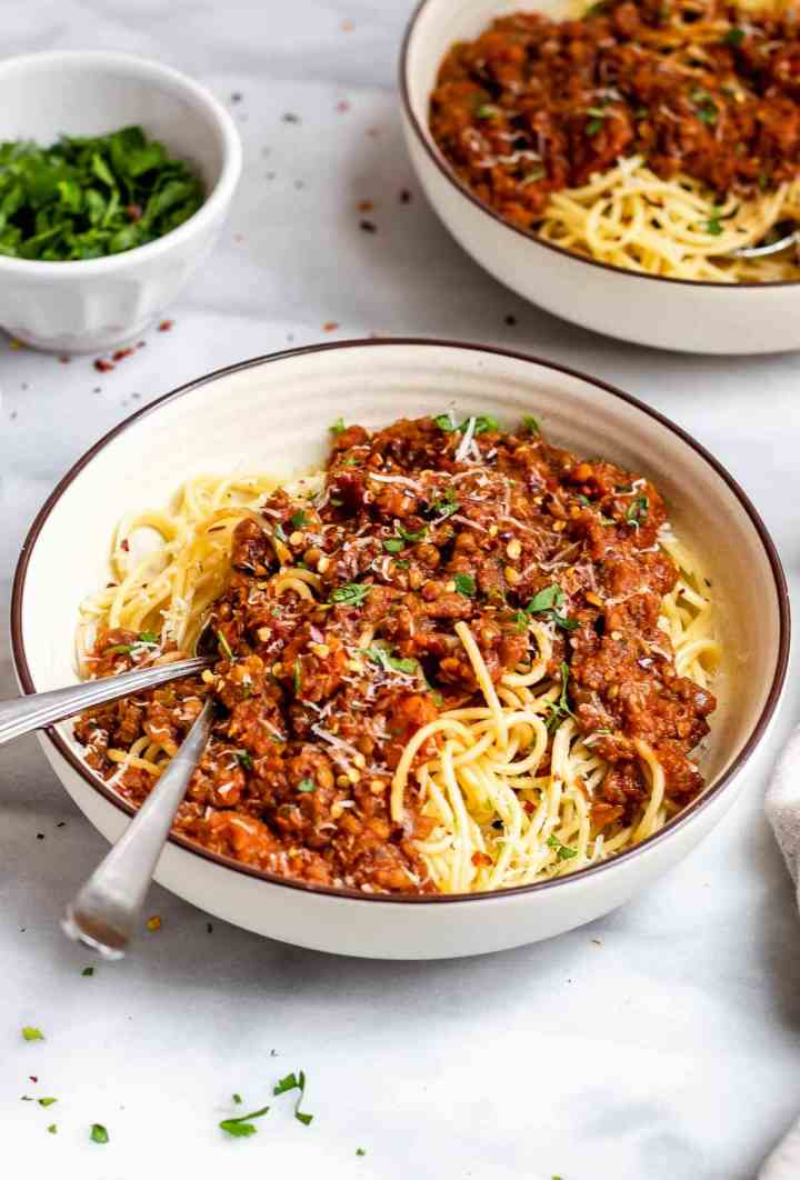 Angled view of the bolognese in two bowls with two forks on the side of the bowl.