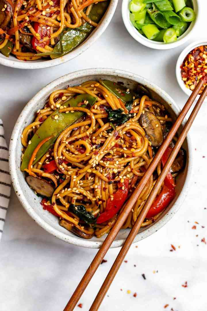Vegetable lo mein with red pepper flakes and chopsticks on the side.