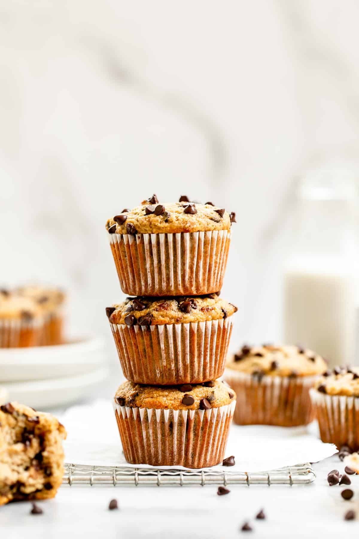 Three almond flour banana muffins stacked on each other with milk in the back.