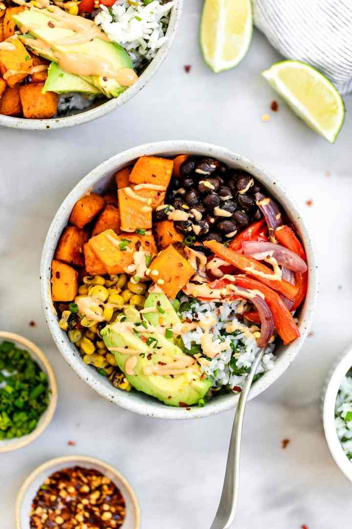 Two bowls with the roasted veggies, sweet potato and black beans.
