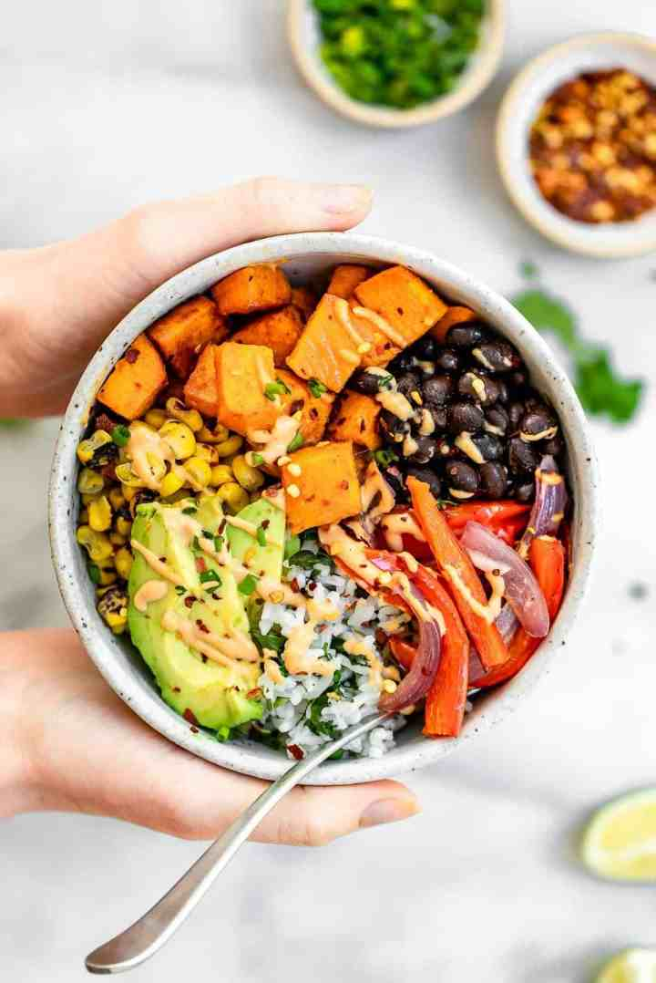 Hand holding the burrito bowl with roasted veggies and sweet potato.