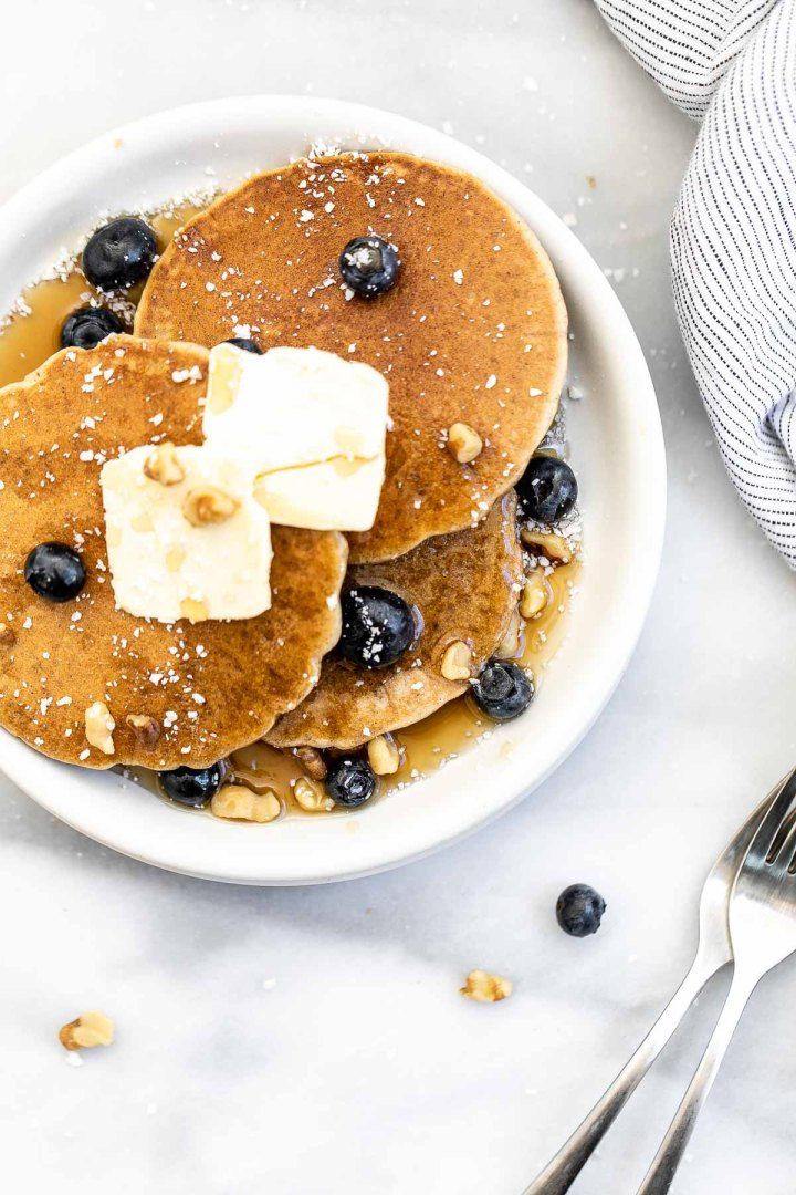 Overhead shot of oat flour pancakes with butter and blueberries on top.