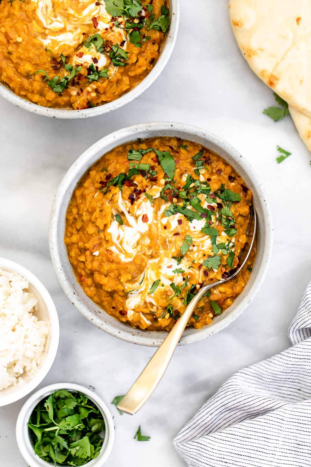 One bowl of lentil curry with yogurt and cilantro on top with a spoon on the side.