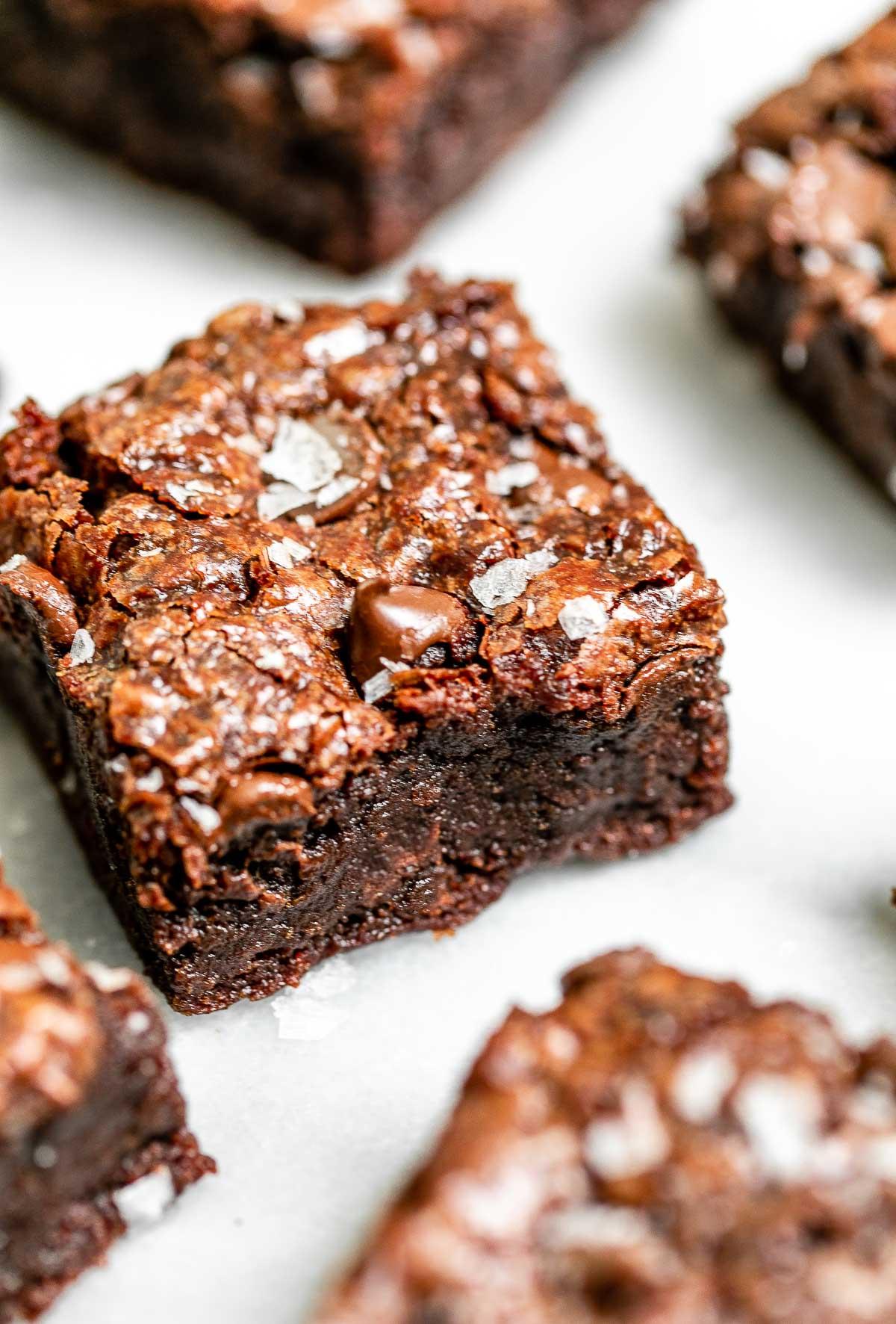 Vegan brownies on a marble backdrop with sea salt sprinkled on top.