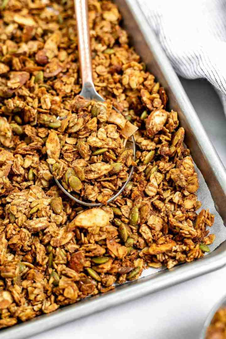 Up close image of the final gluten free granola on a baking tray with a spoon.