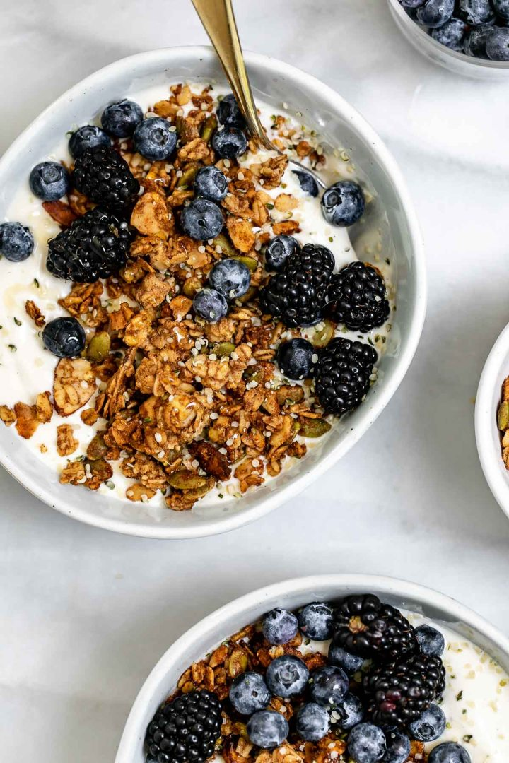 Two bowls with yogurt, granola and berries.