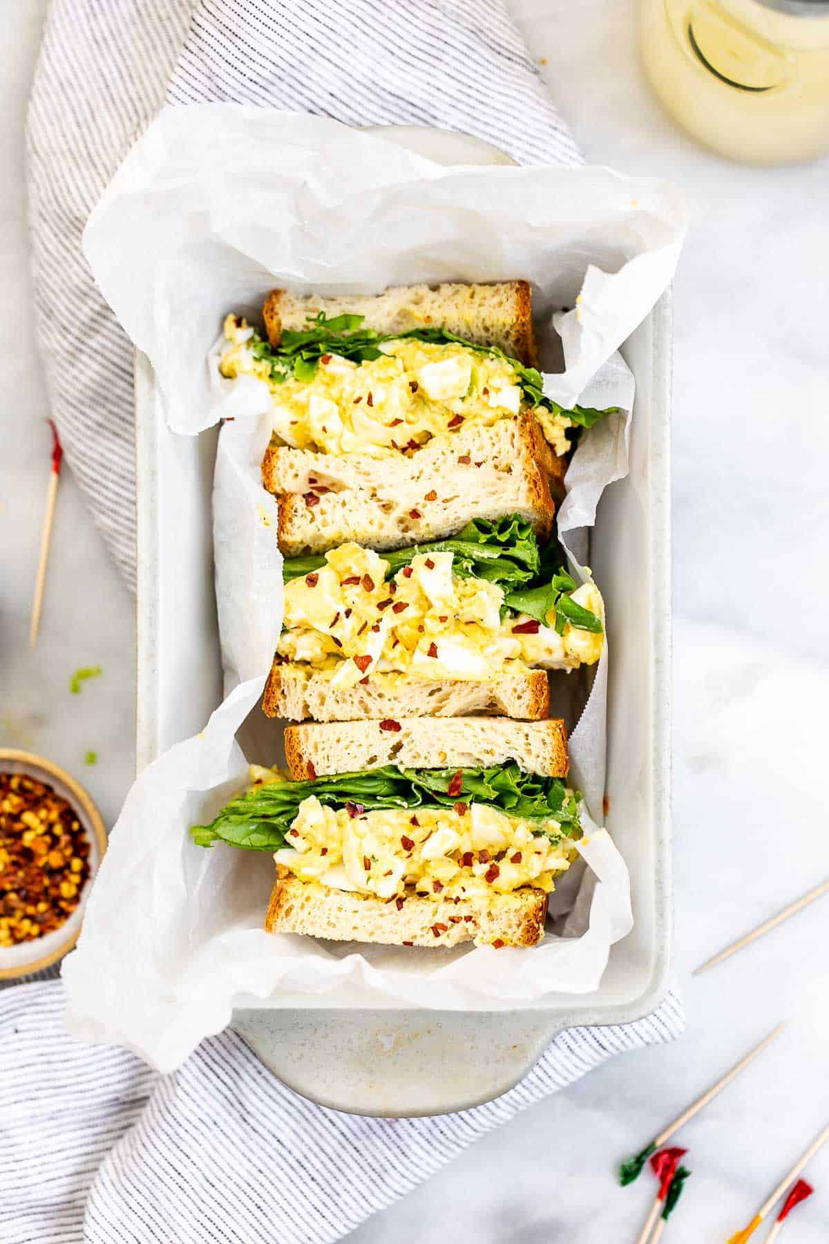 Egg salad sandwiches in a bread pan with parchment paper.