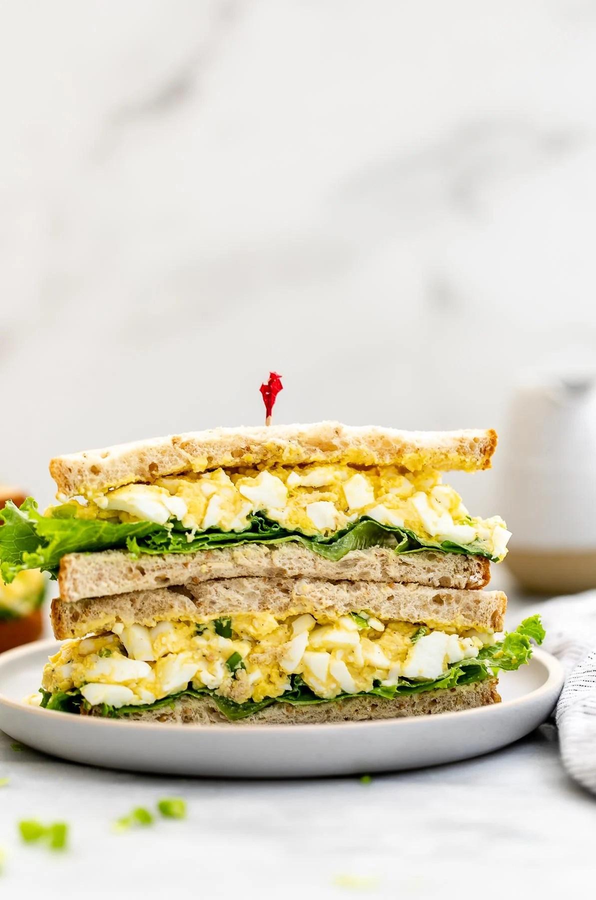 Healthy egg salad sandwich cut in half on a small plate.
