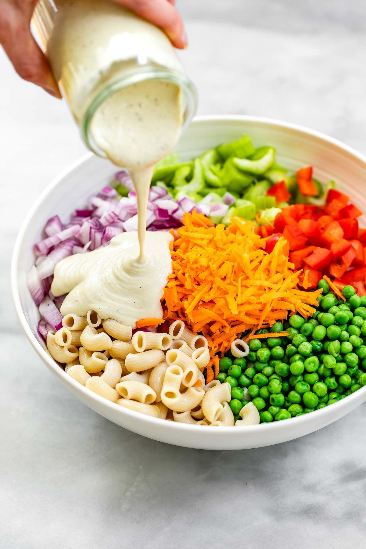 Pouring the dressing on the salad with veggies.