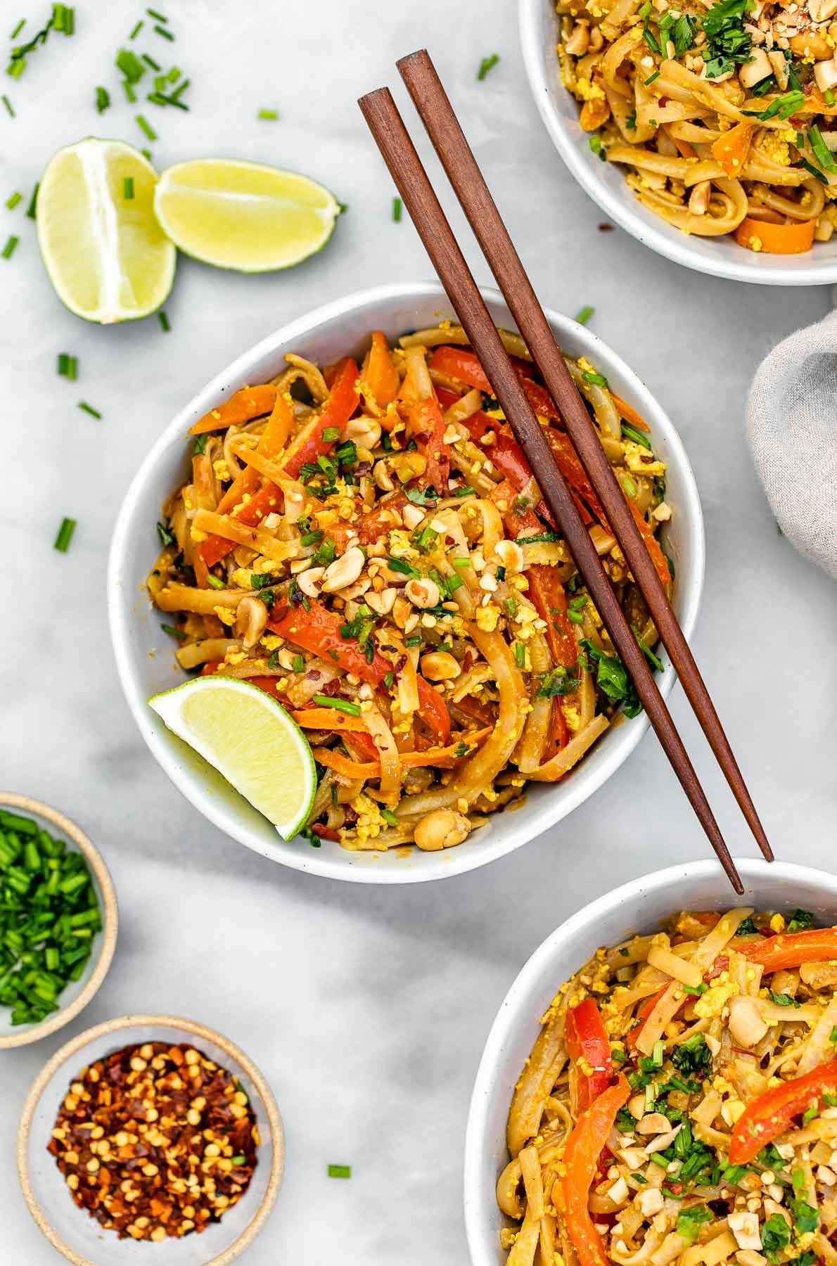 Vegan pad thai in three bowls with chopsticks on top.