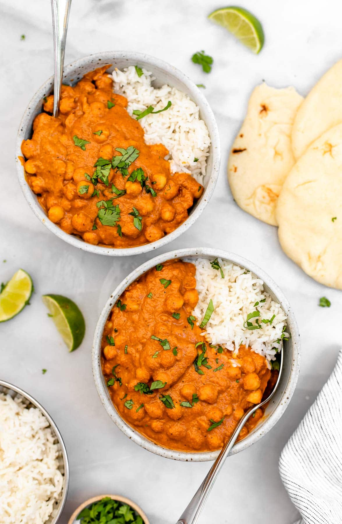 Two bowls with white rice, vegan tikka masala and naan on the side.