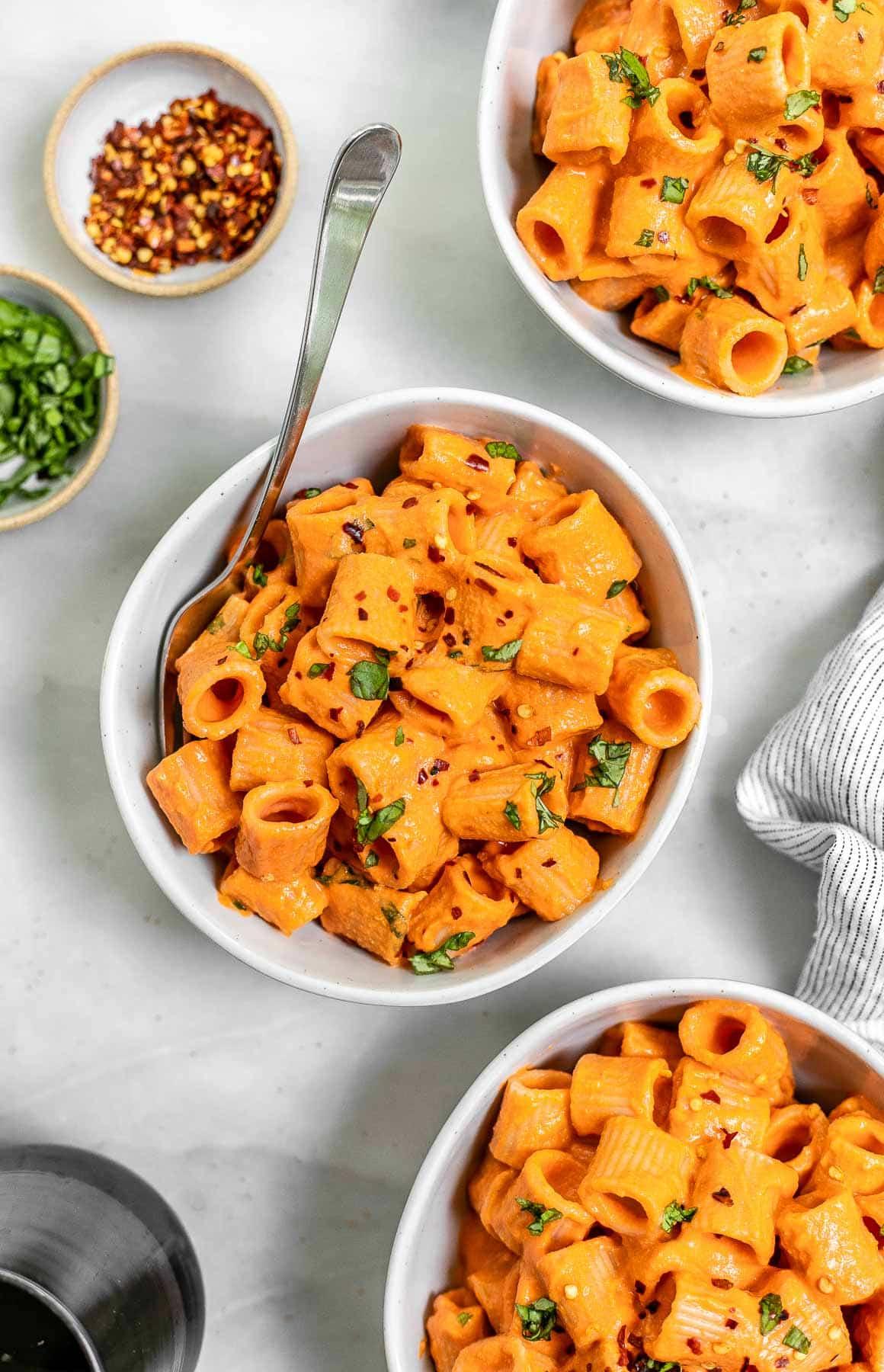 Three bowls of vegan vodka pasta with fresh basil on top.