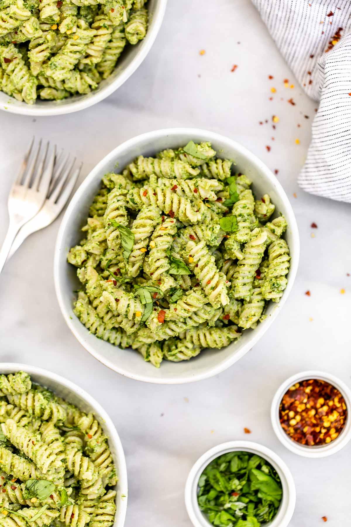 Vegan nut free pesto pasta with fresh basil in a white bowl.