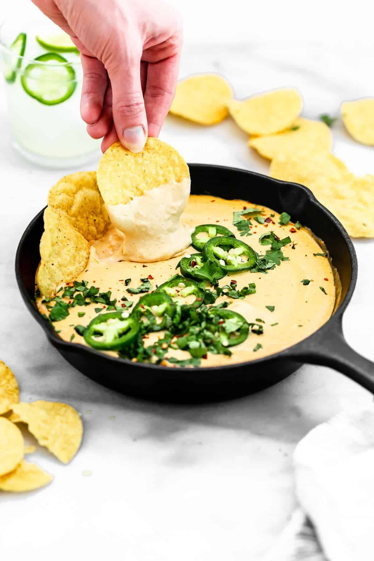 Dipping in a chip in the vegan queso.