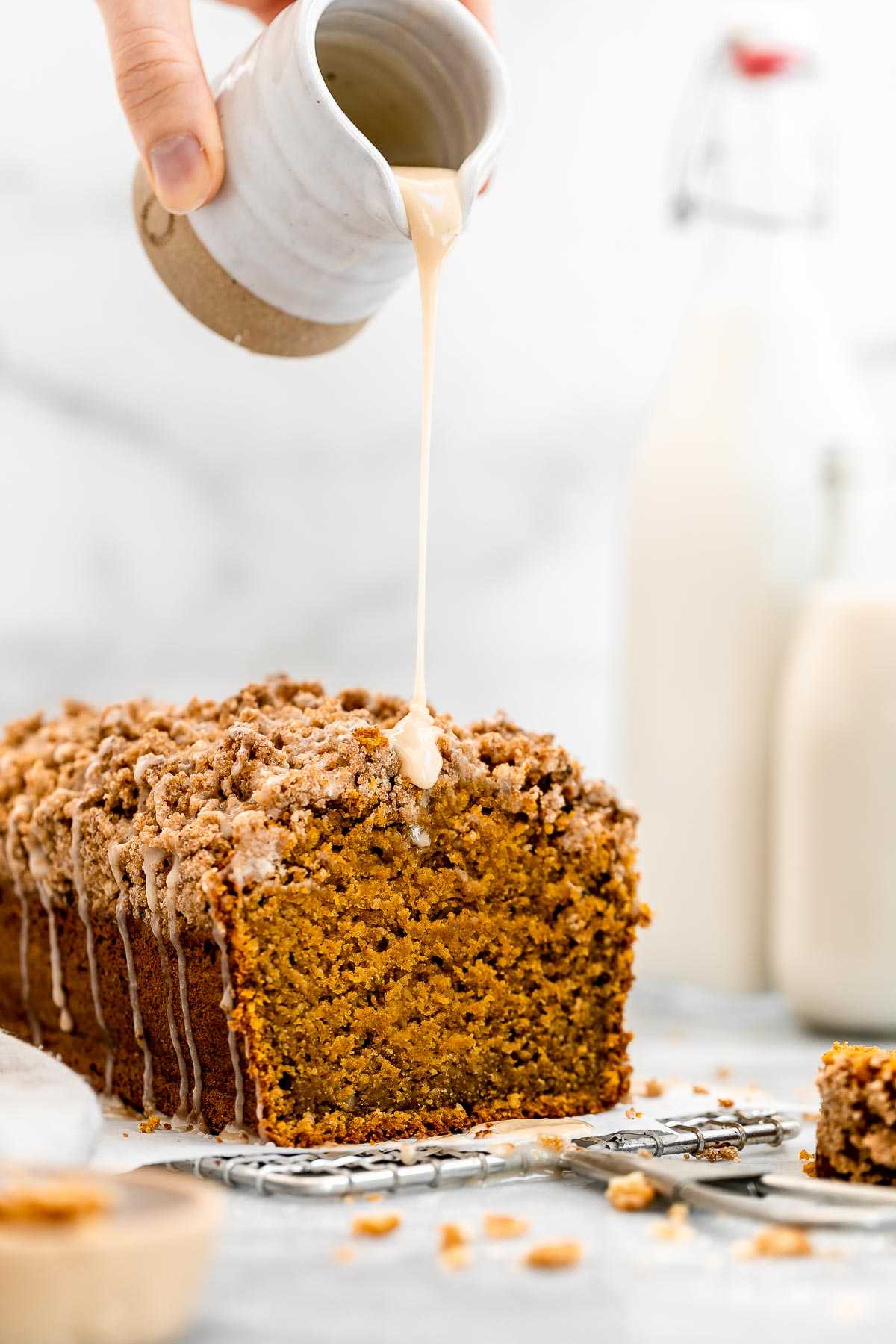 Pouring the maple glaze on top of the healthy pumpkin bread.