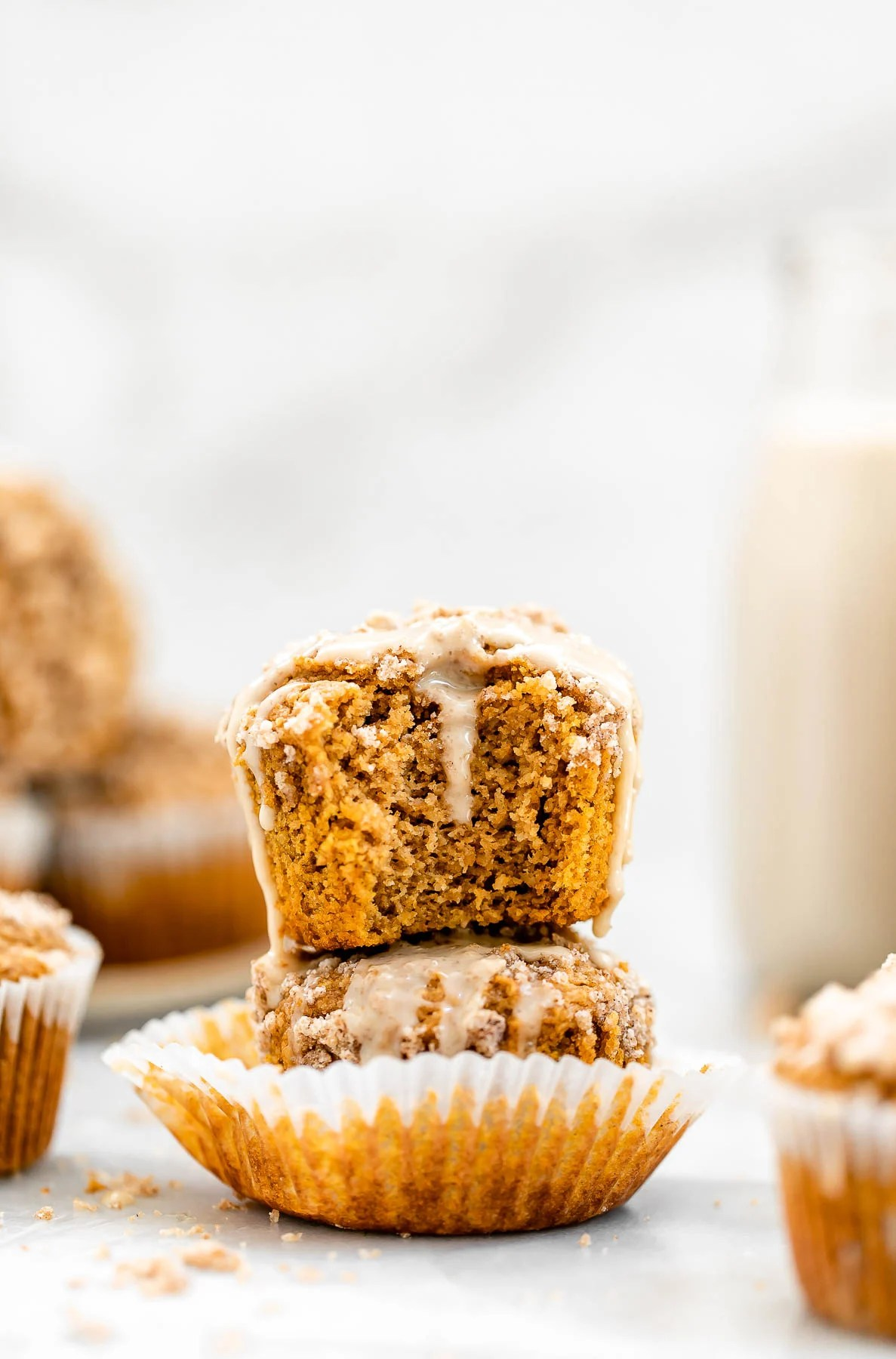 Two sweet potato muffins on top of each other with maple glaze.