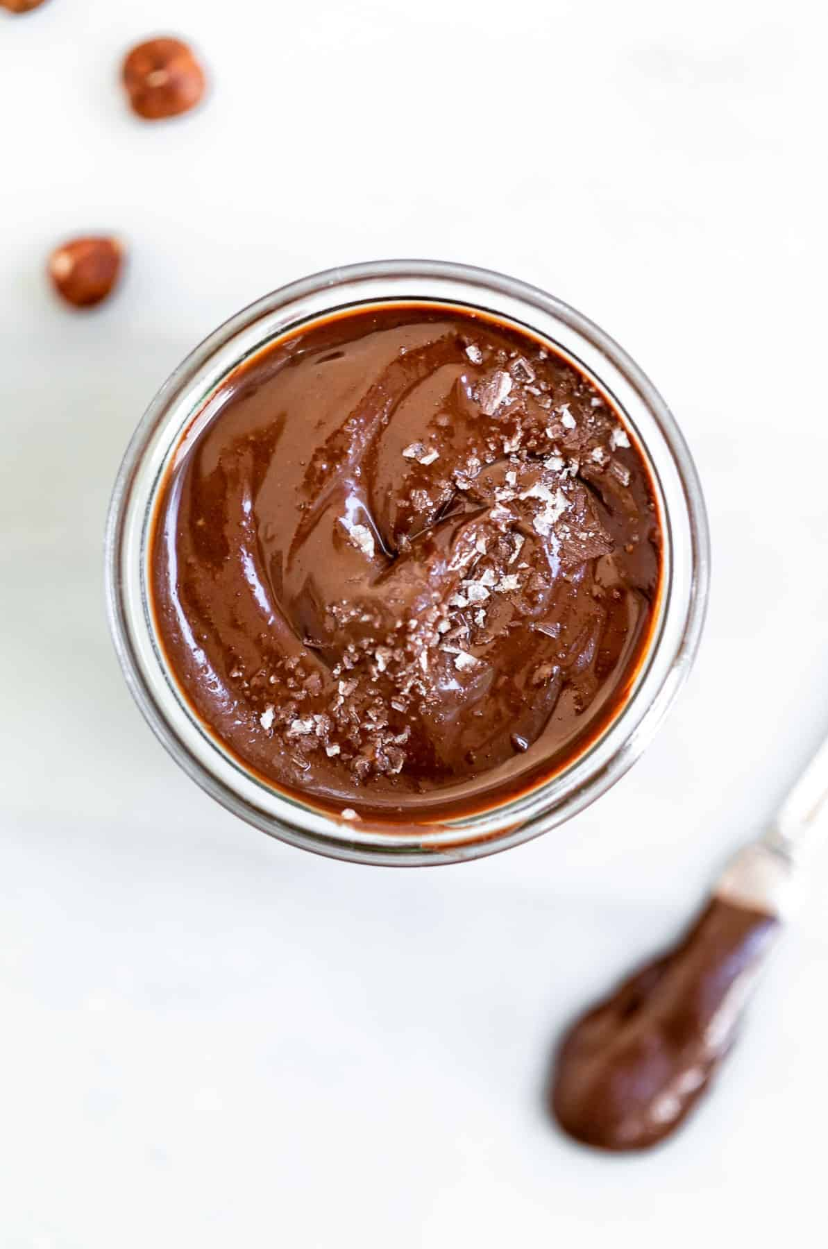 Vegan nutella in a jar with sea salt on top.