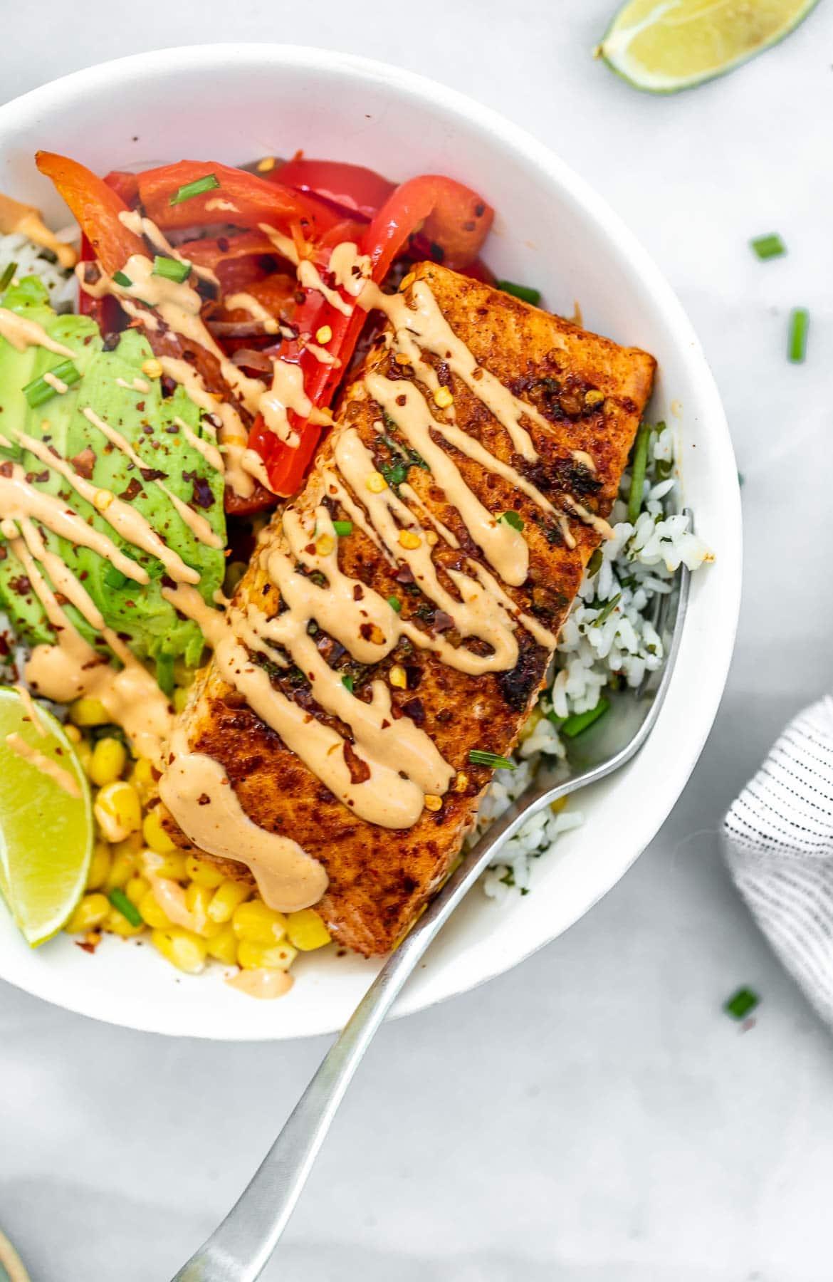 Chili lime salmon bowls with tahini dressing on top.