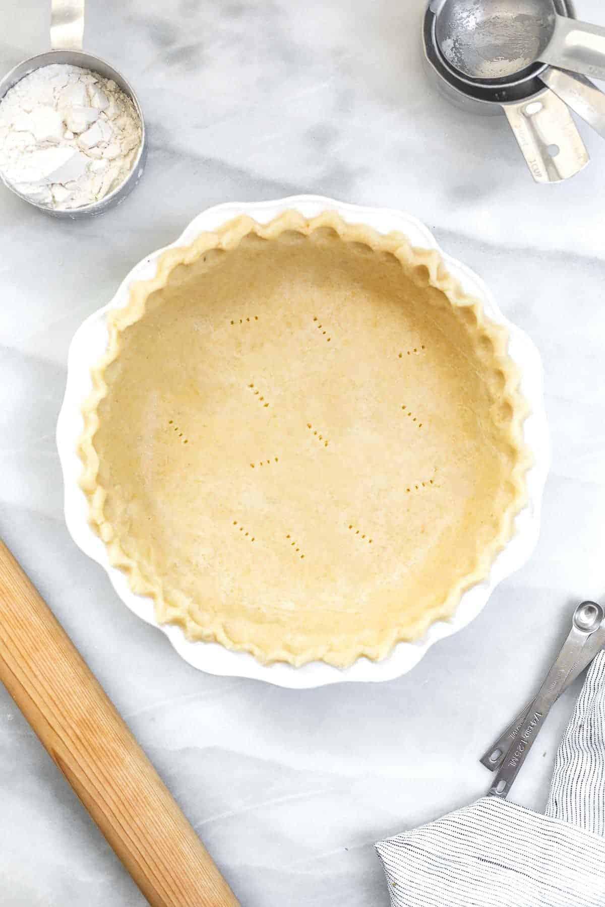 Gluten free pie crust on a marble backdrop.