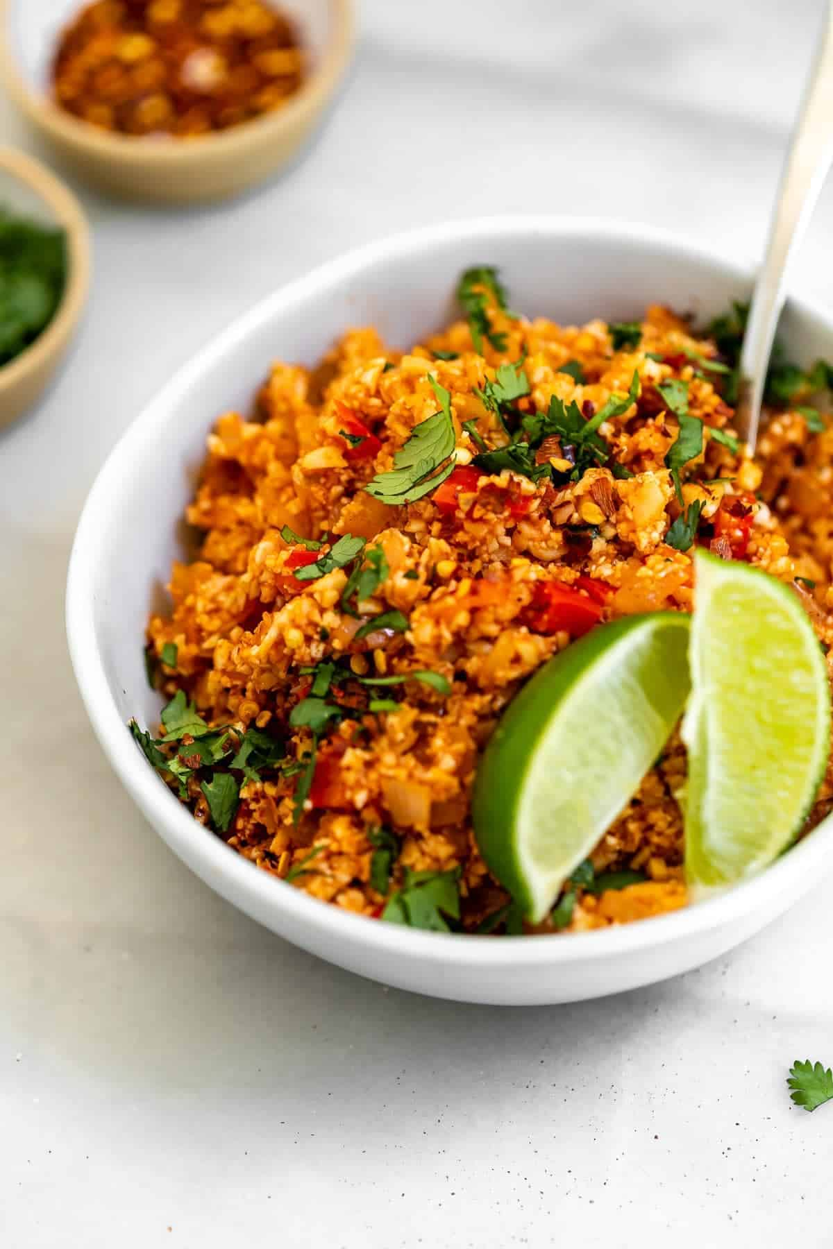 Vegan spanish mexican cauliflower rice in a bowl with cilantro.