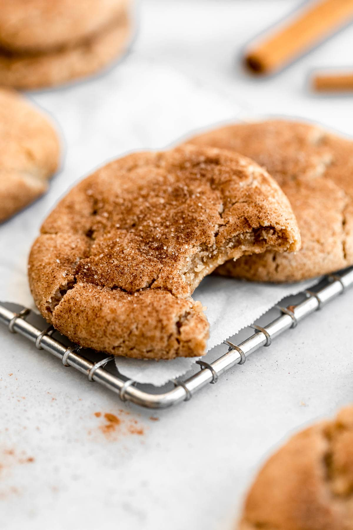 Vegan snickerdoodles on a cooling rack with a bite taken out.