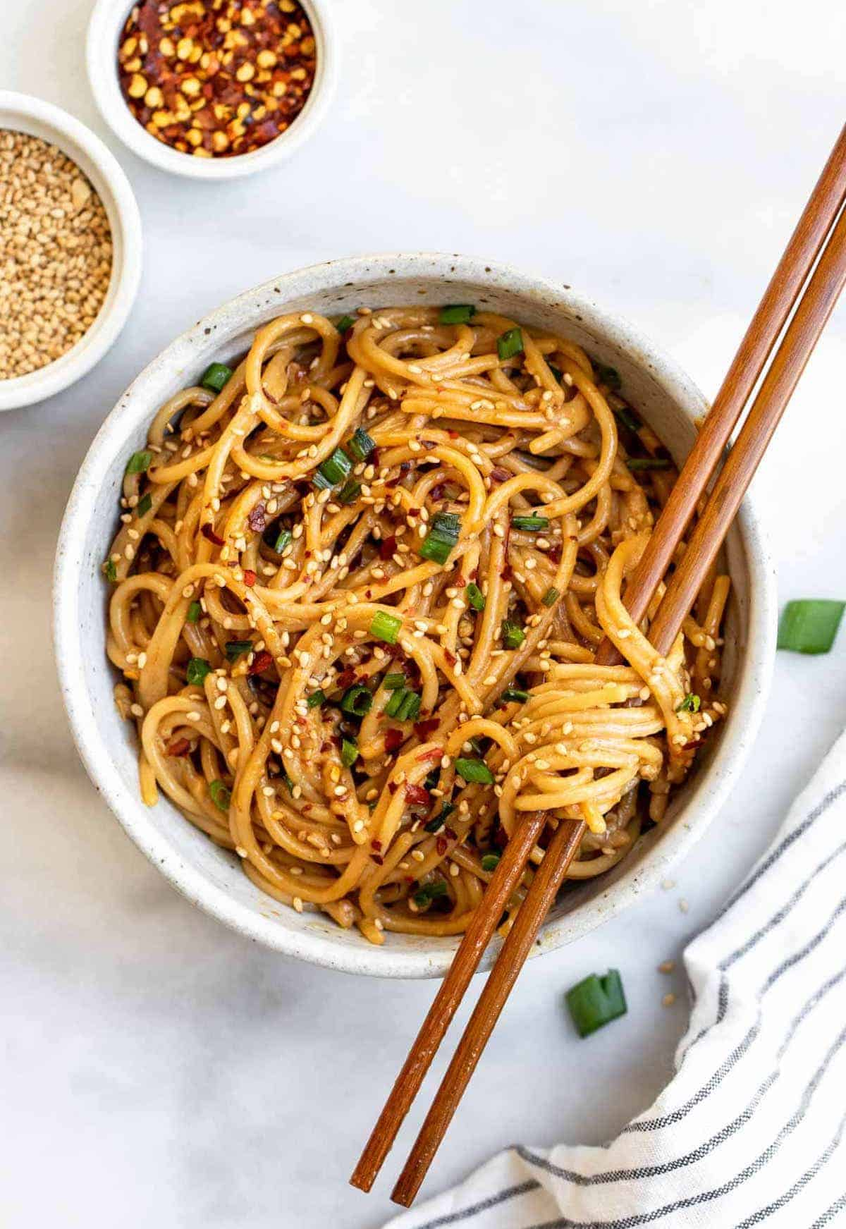 Overhead shot of one bowl with the sesame noodles with chopsticks going through the noodles.