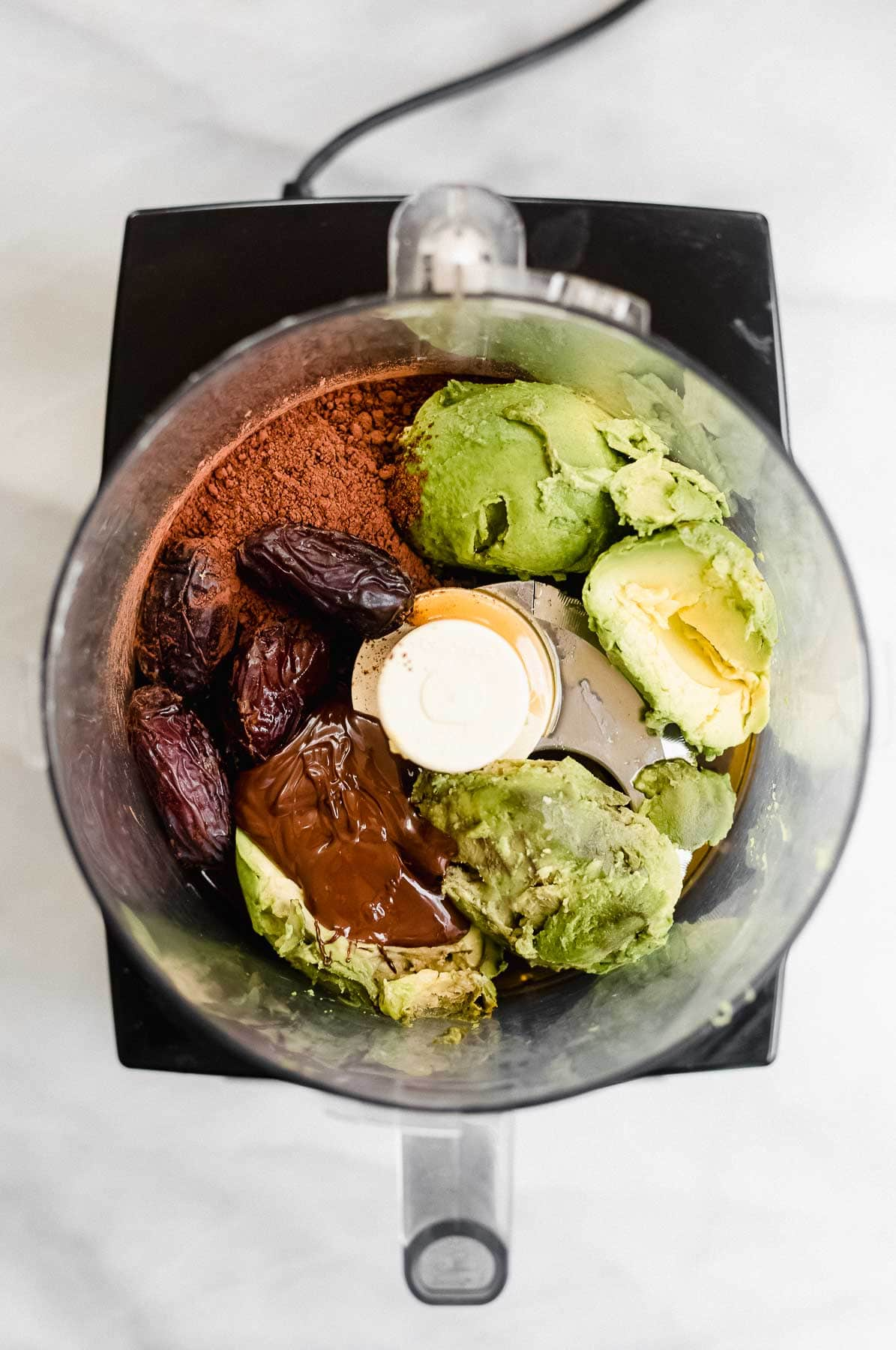 Ingredients for the avocado mousse in a food processor.