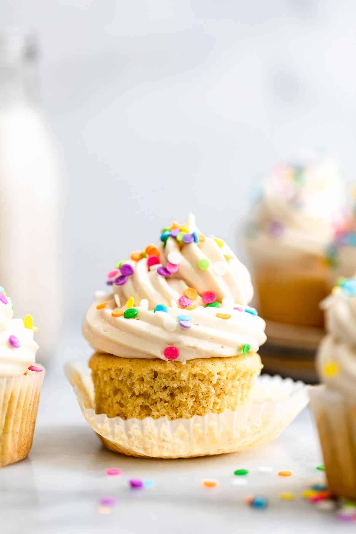 Gluten free vanilla cupcakes with rainbow sprinkles on top with milk in the back.