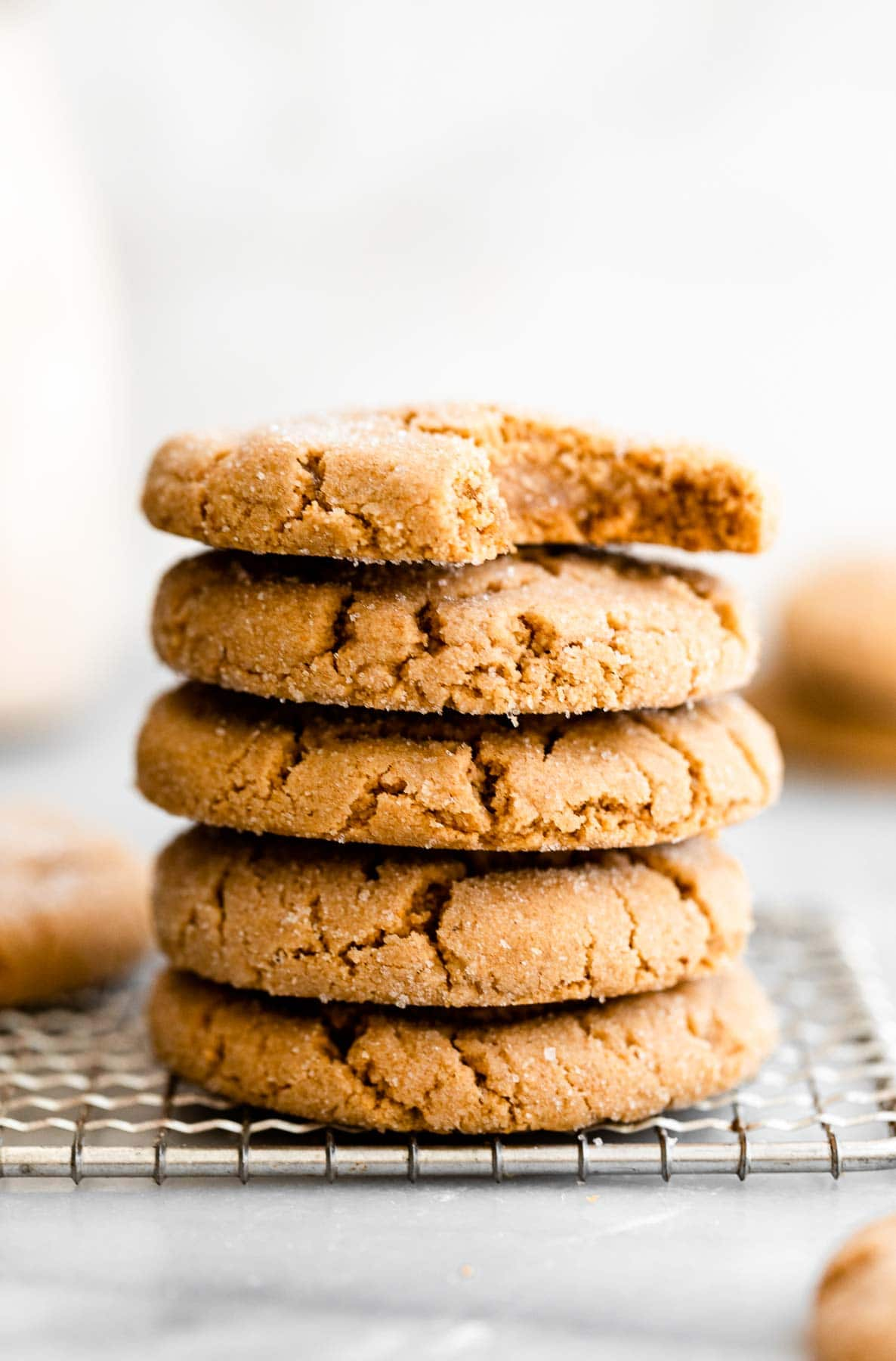 Vegan peanut butter cookies stacked one each other on a cooling rack.