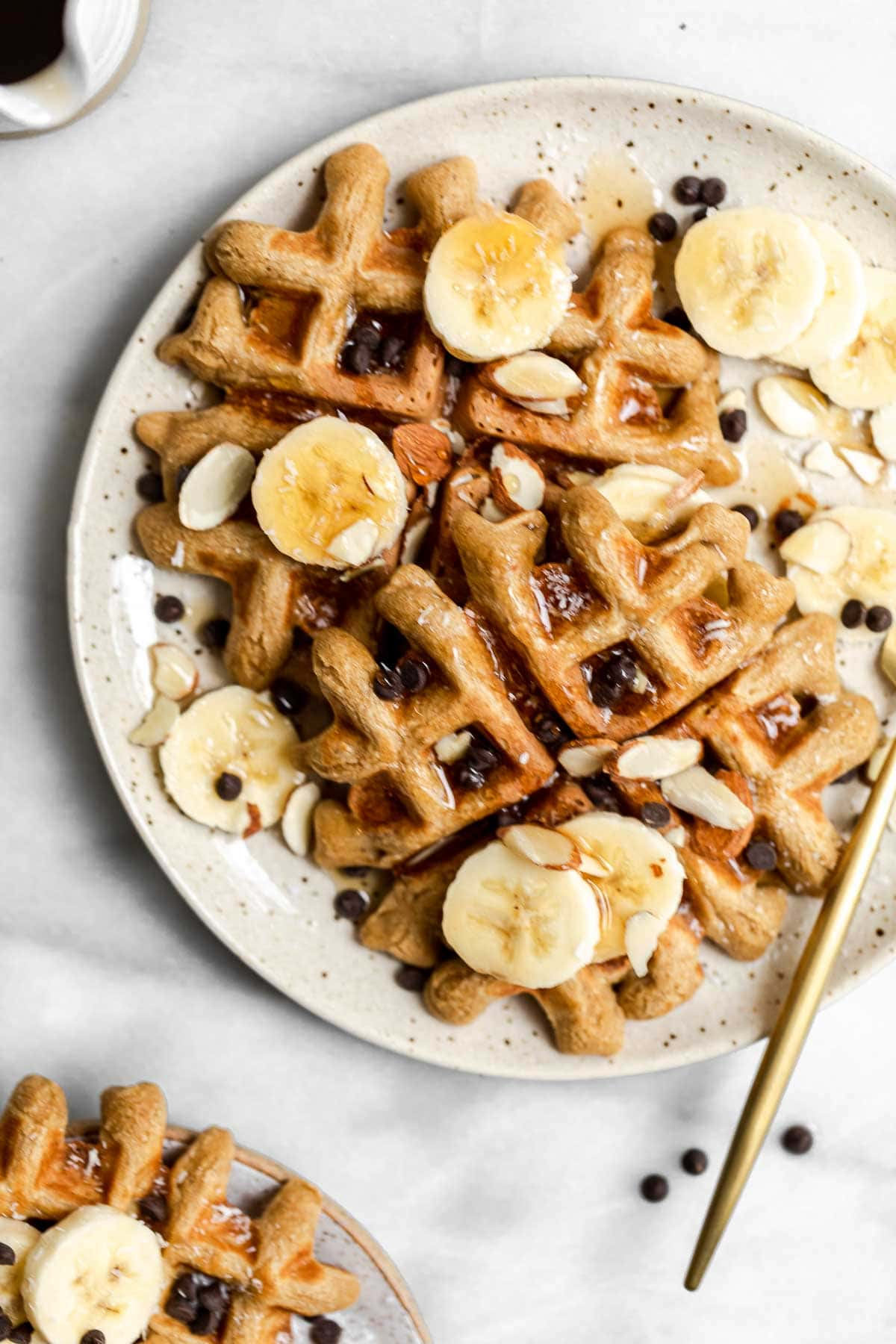 Speckled plate with peanut butter waffles and banana slices.