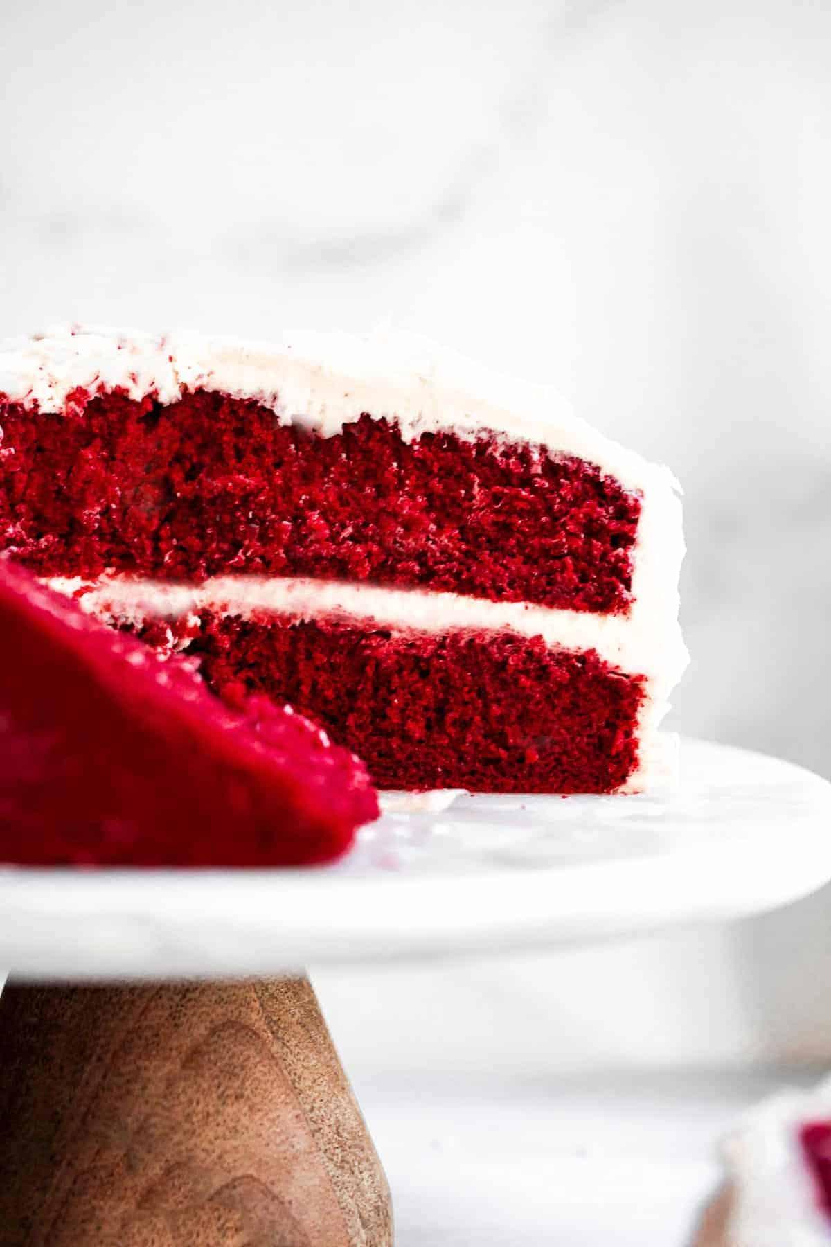 Red velvet cake sliced on a cake stand.