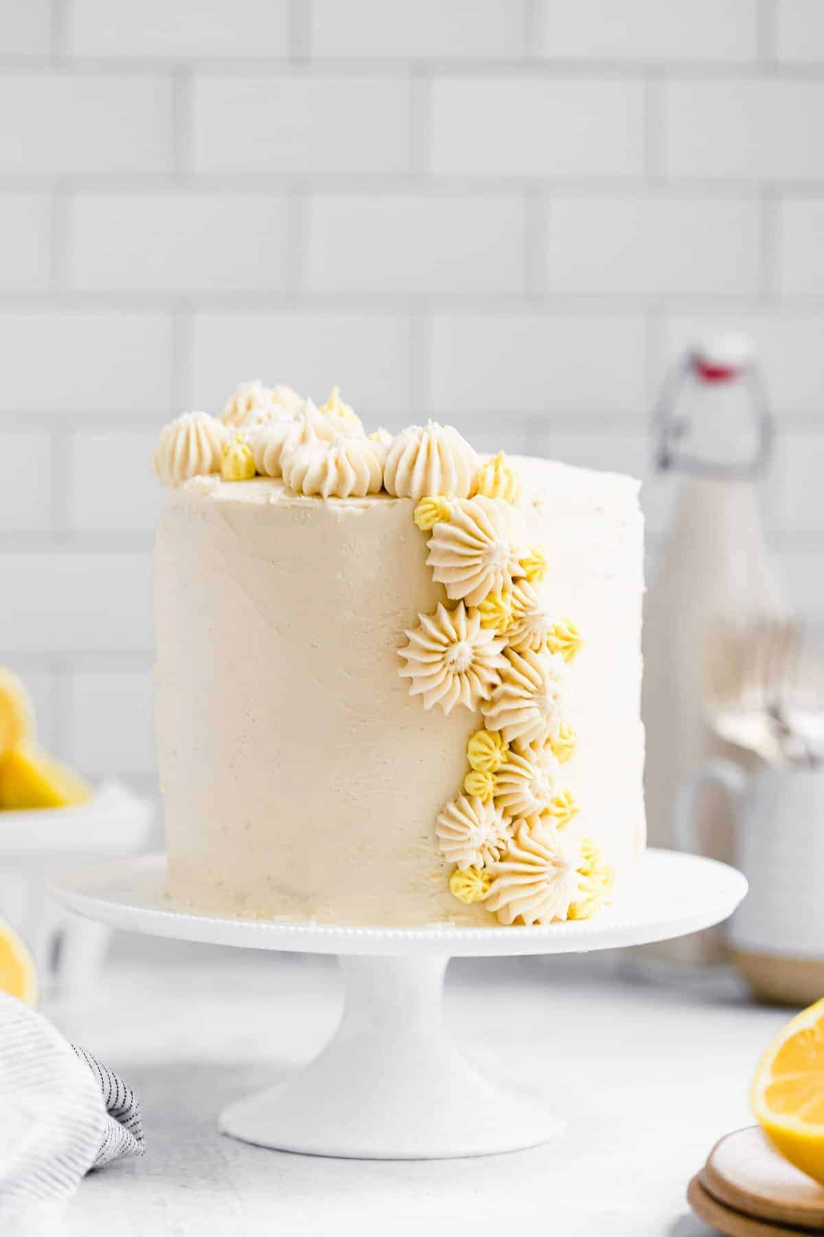 gluten free lemon cake on a cake stand with lemon frosting