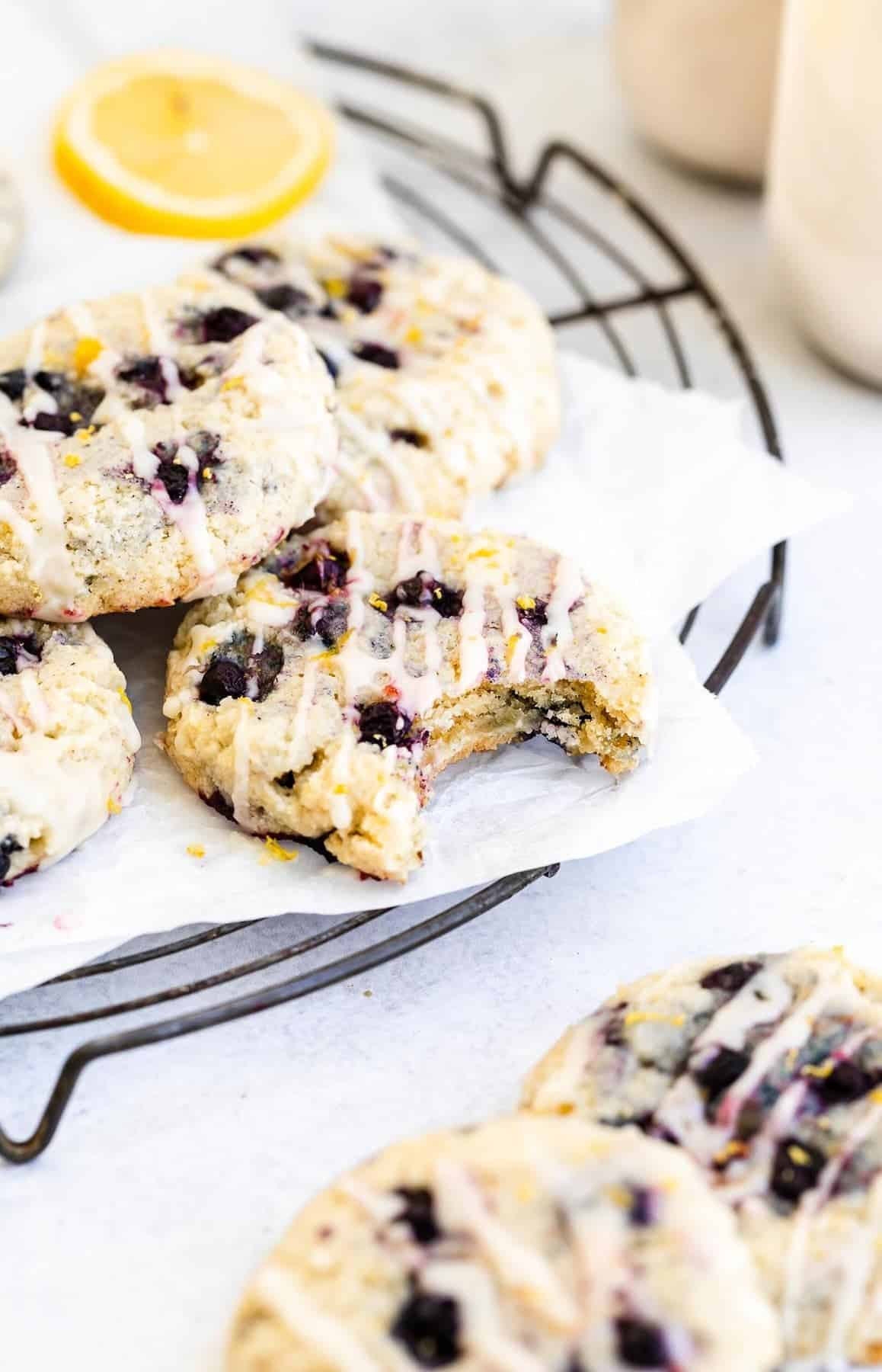 vegan lemon blueberry cookies with a bite taken out on a wire rack