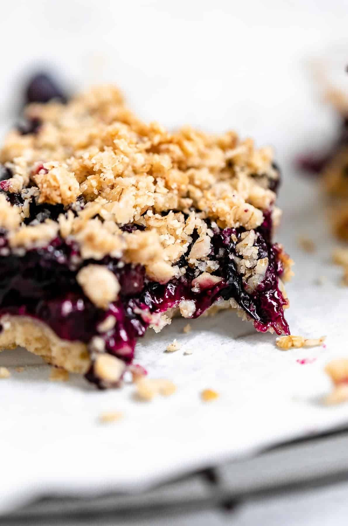 one blueberry crumble bar with a bite taken out