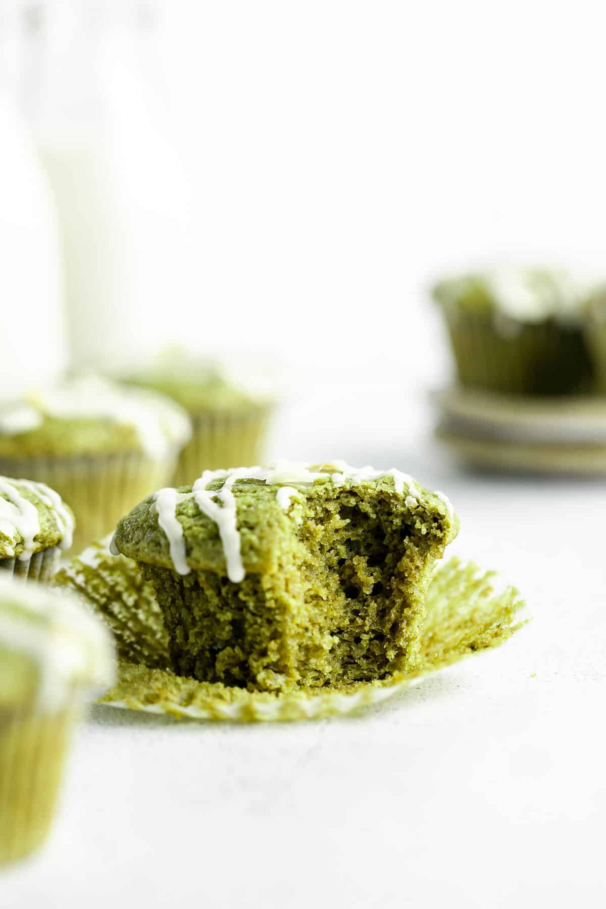 matcha muffins with one bite taken out to show fluffy texture