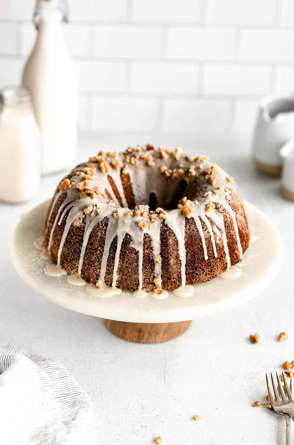 gluten free apple bundt cake on a cake stand with maple icing