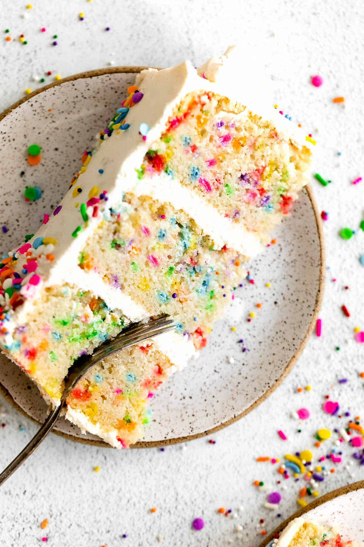 gluten free birthday cake slice on a plate with a fork