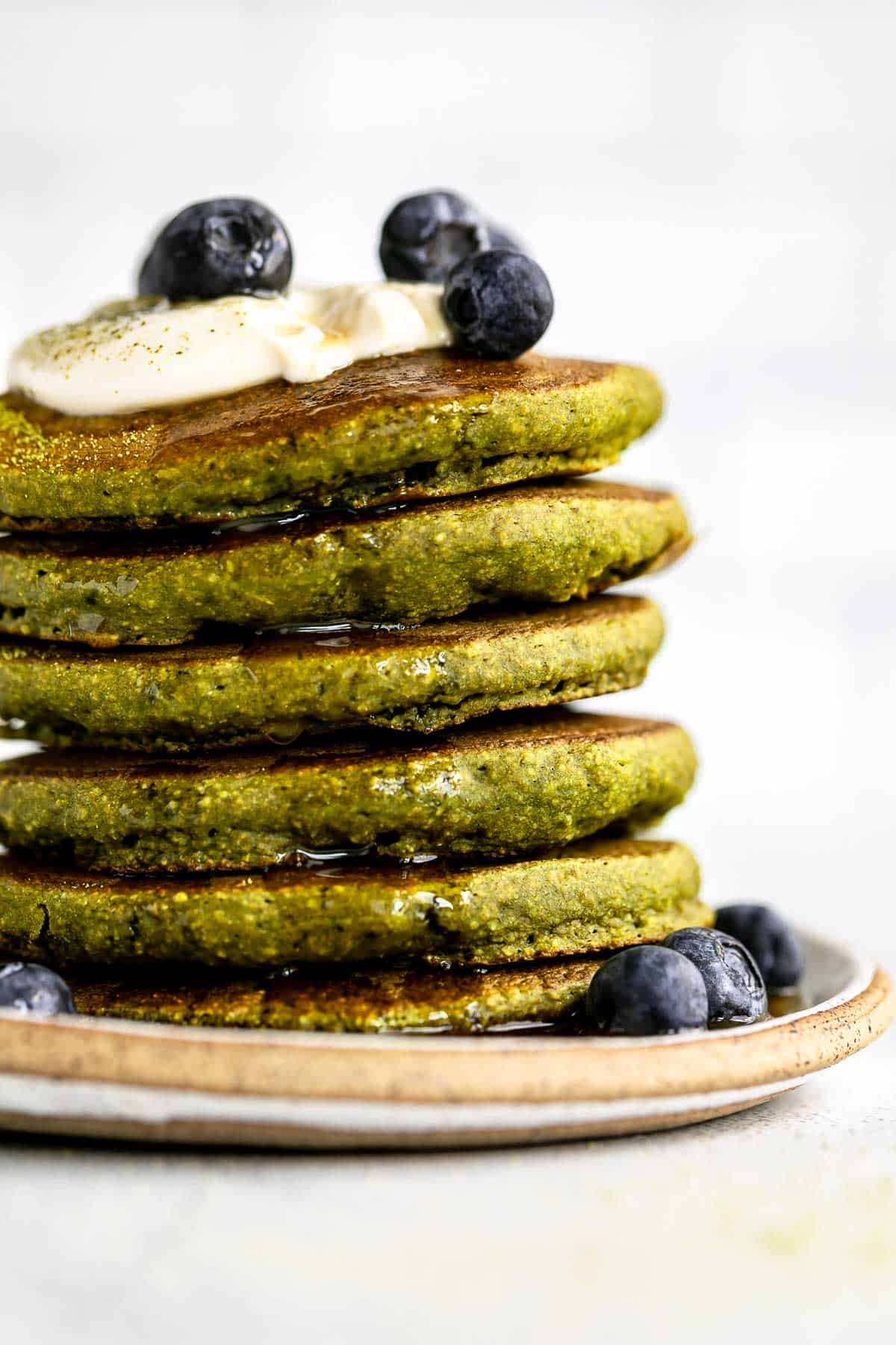 oat flour matcha pancakes on a plate with blueberries