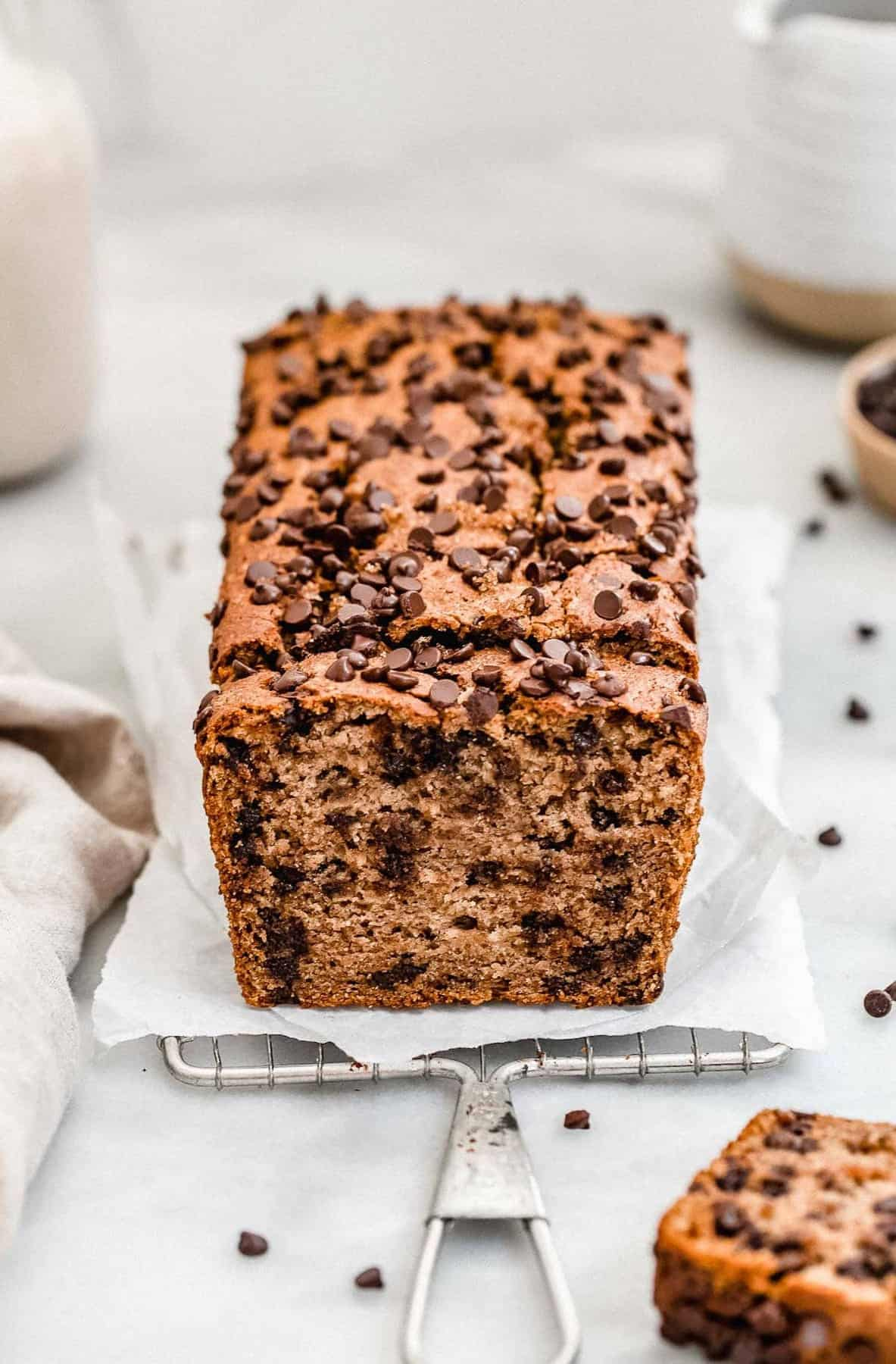 Vegan chocolate chip banana bread on a cooling rack with milk.