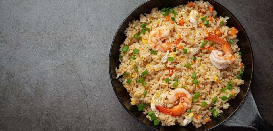 Shrimp fried rice in a black pan on a grey countertop.
