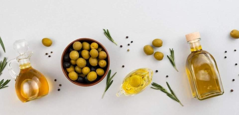 Olive oil, apple cider vinegar, parsley on a table. Apple cider vinegar salad dressing ingredients on a white table.