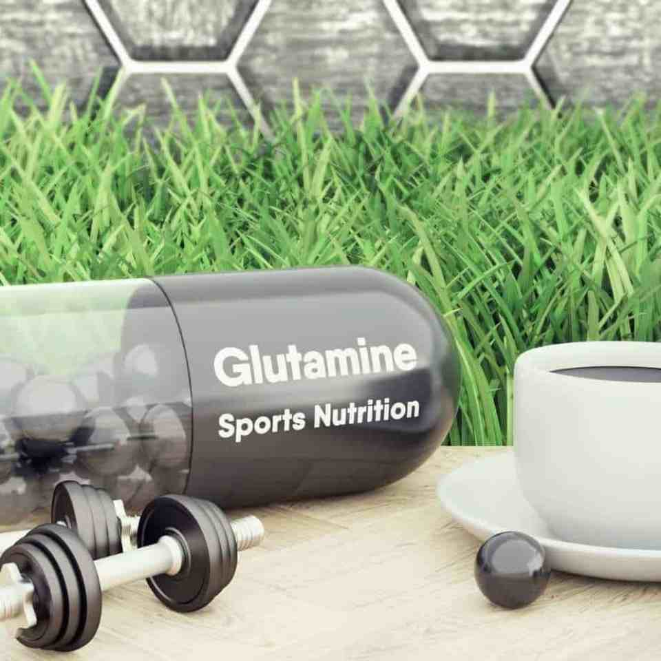 Glutamine sports nutrition supplements on a table with dumbells and coffee.