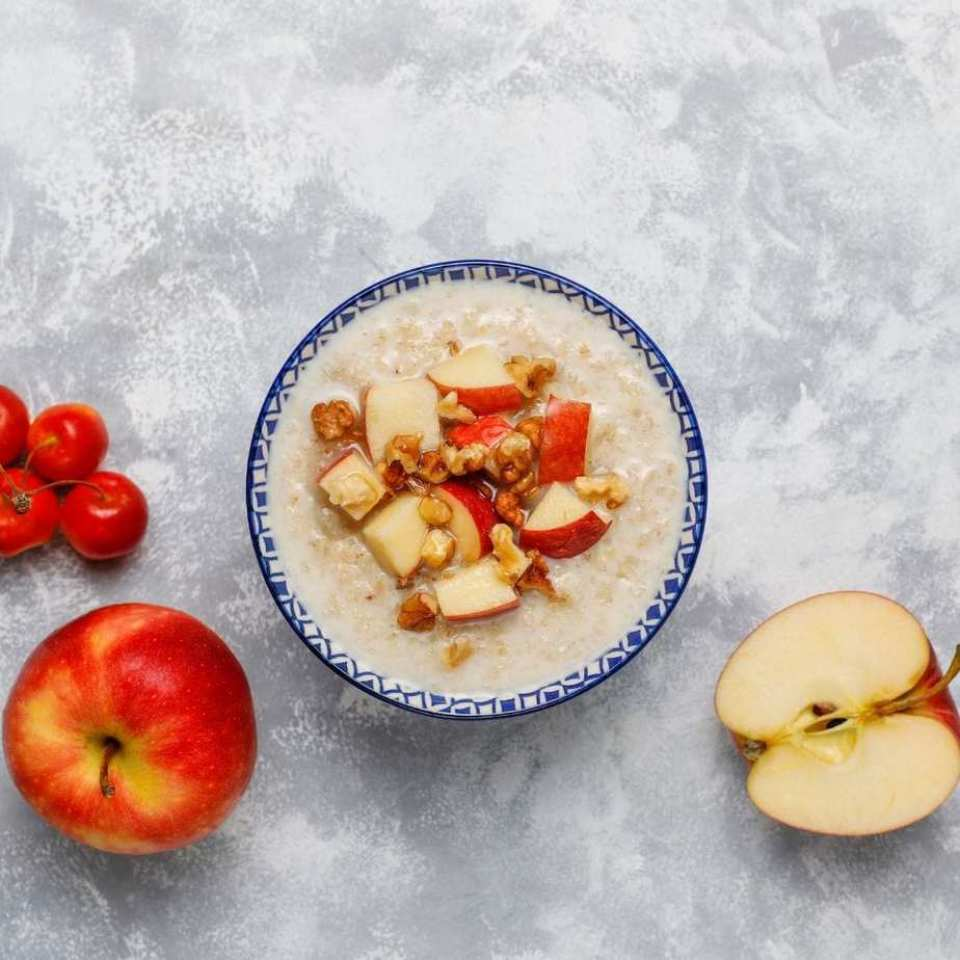 Healthy snack of oatmeal in a bowl with honey, red apple slices, and walnuts.
