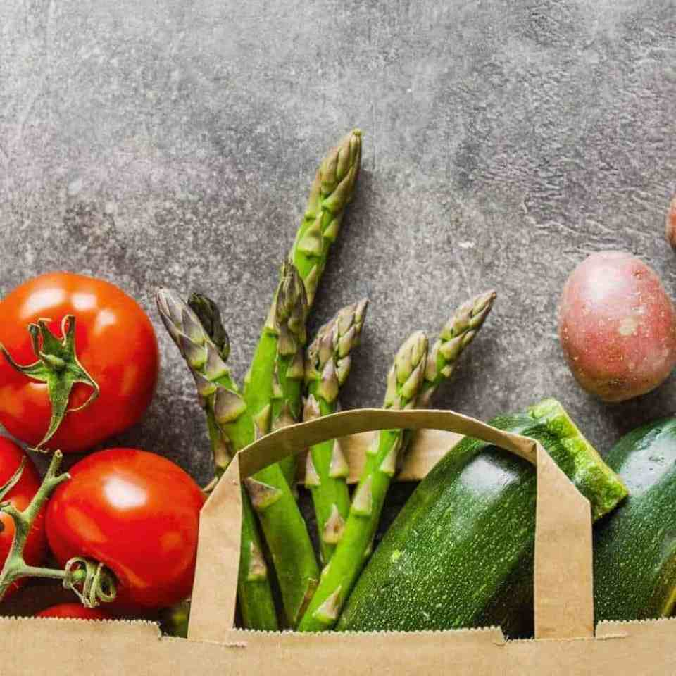 Tomatoes, asparagus, potatoes, and zucchini in a brown shopping bag, which is how to eat healthy on a budget and lose weight.