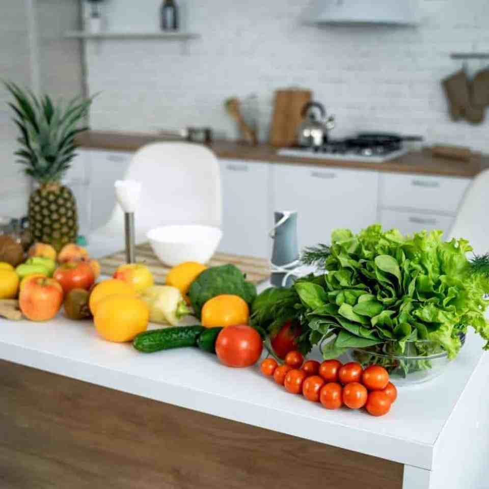 Healthy eating tips with fruits and vegetables on a white countertop.