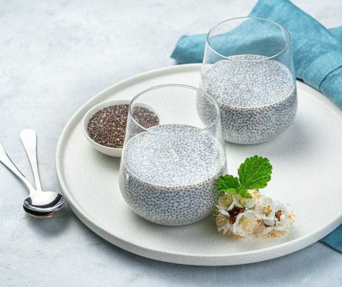 Healthy low carb breakfast of chia pudding with a blue napkin and flowers.