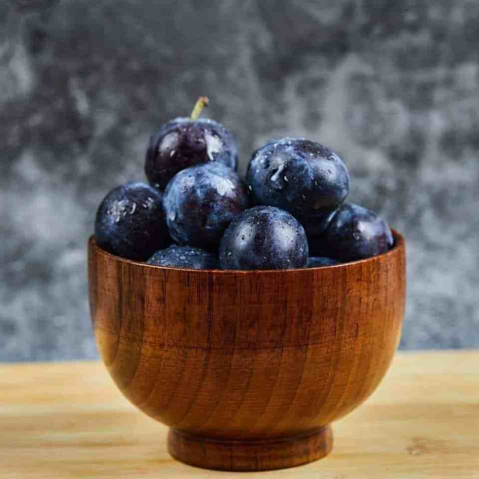 Wooden bowl filled with the vitamin and antioxidant rich fruit, plums.
