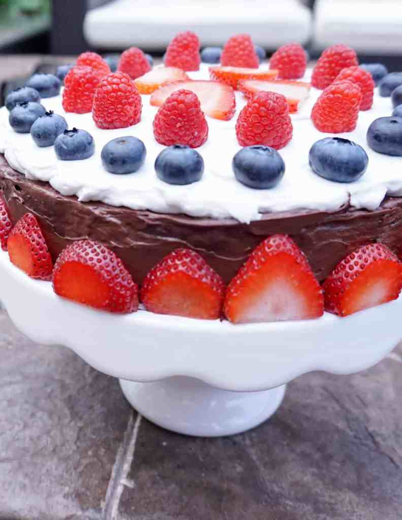 Vegan chocolate sweet ptoato cake on white cake stand with strawberry border and mixed berries on top for a red white and blue celebration.