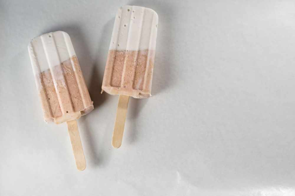Fresh rhubarb and coconut cream are sweetened with dates and maple syrup for this refined sugar free and dairy free Paleo Rhubarb Coconut Popsicles recipe